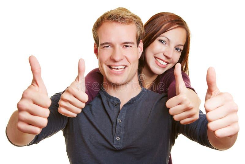 Pares felices del ganador que sostienen los pulgares imagen de archivo