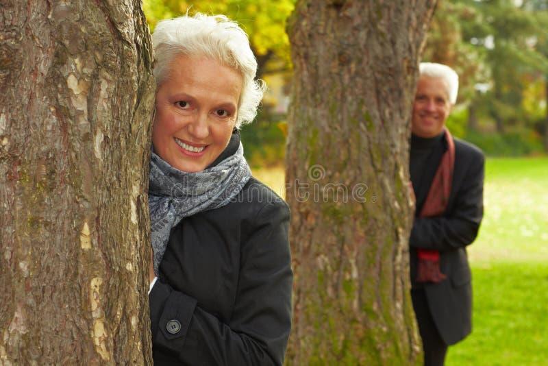 Pares felices detrás de árboles imagen de archivo libre de regalías