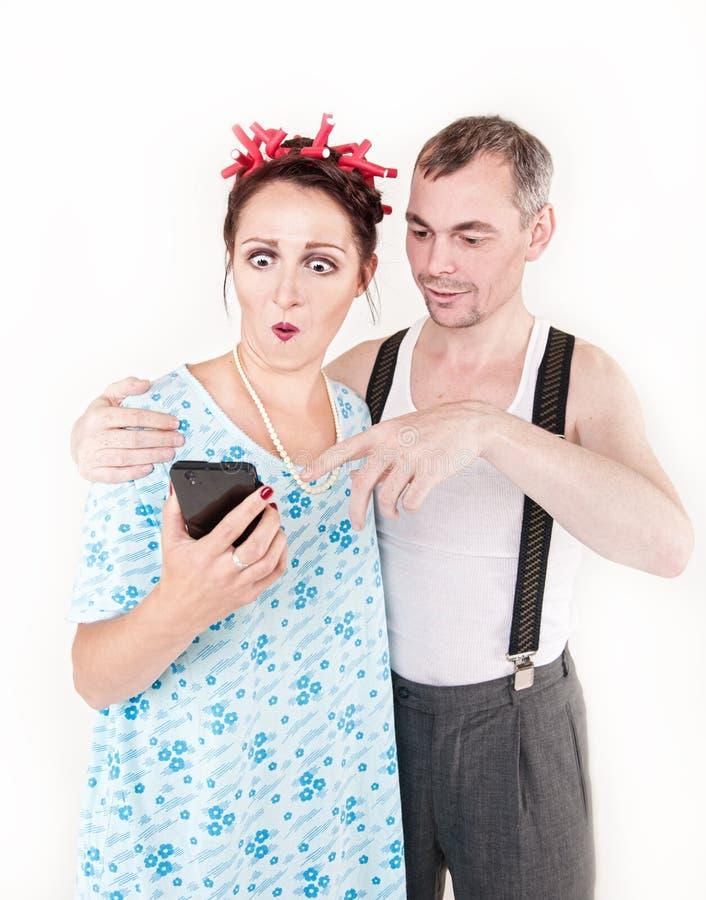 Pares felices divertidos de la familia usando smartphone foto de archivo libre de regalías