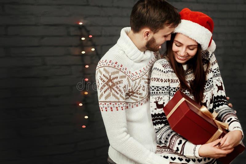Pares felices elegantes con la actual sonrisa del rojo grande suavemente abrazando imagen de archivo libre de regalías