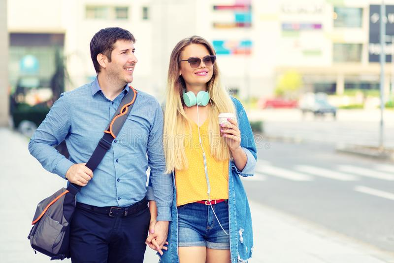 Pares felices elegantes modernos que caminan junto en la calle del centro de ciudad que celebra las manos y la sonrisa foto de archivo libre de regalías