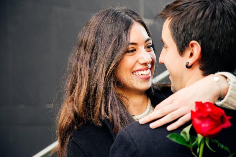 Pares felices en amor con una rosa en la calle imagen de archivo