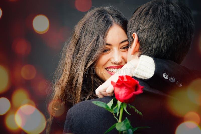 Pares felices en amor con una rosa que abraza en la calle imagenes de archivo