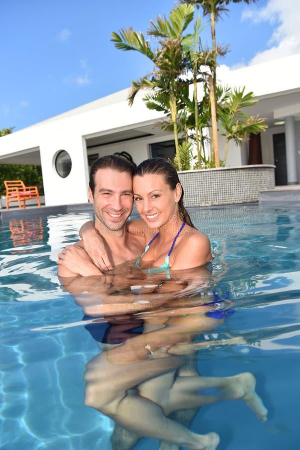 Pares felices en amor en una piscina privada foto de archivo