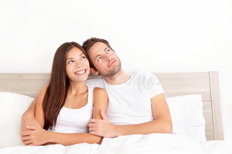 Pares felices en cama foto de archivo