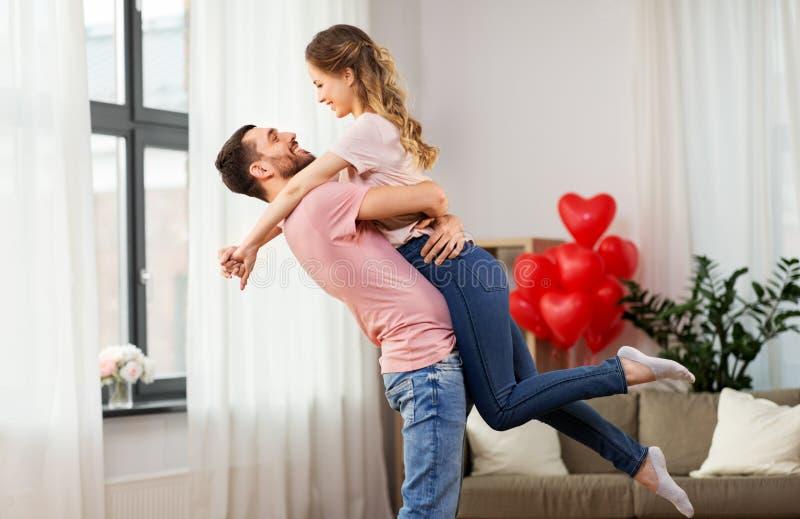 Pares felices en casa en día de San Valentín imagenes de archivo