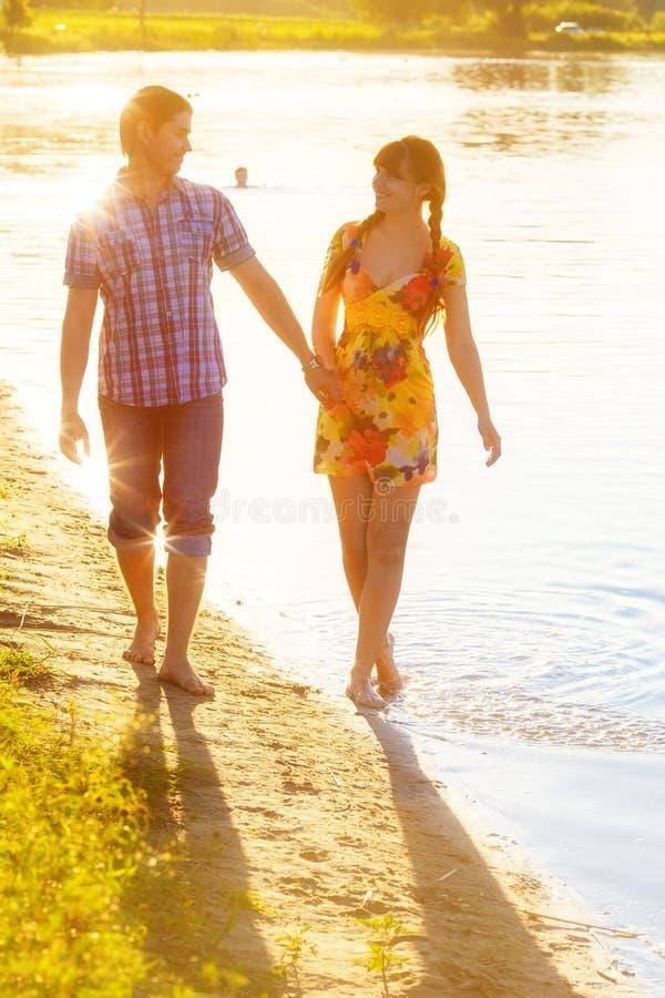 Pares felices en el amor que camina en la playa Vacaciones de verano concentradas imagen de archivo libre de regalías