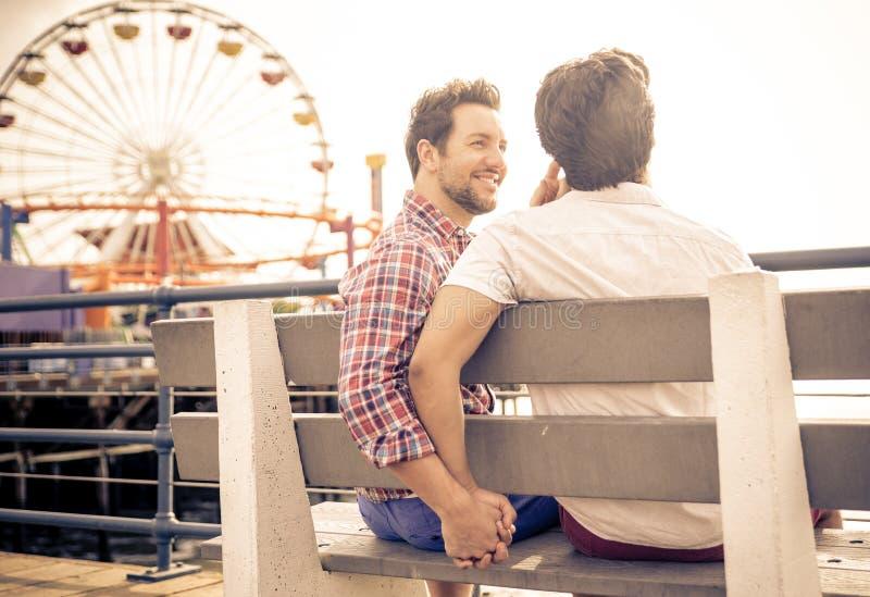 Pares felices en el amor que juega en Santa Mónica en la playa fotos de archivo