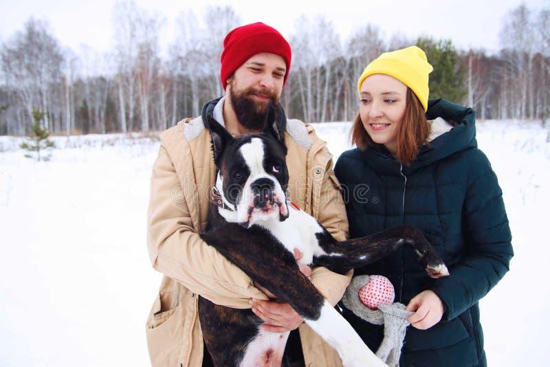 Pares felices en el amor que se divierte en la nieve con su perro del bebé imagenes de archivo