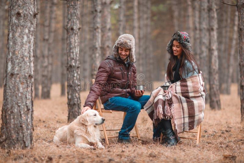 Pares felices en el amor, sentándose en el bosque del otoño que bebe té caliente y que juega con un perro fotografía de archivo