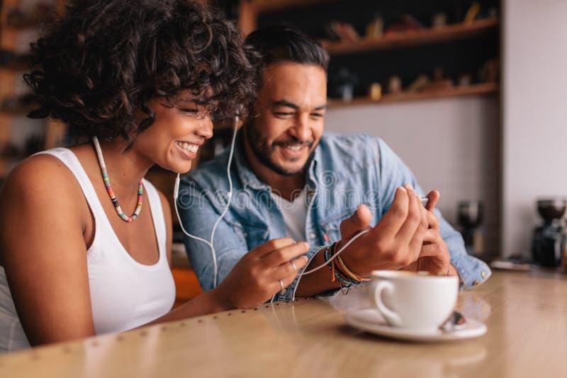 Pares felices en el café que tiene charla video en el teléfono móvil foto de archivo