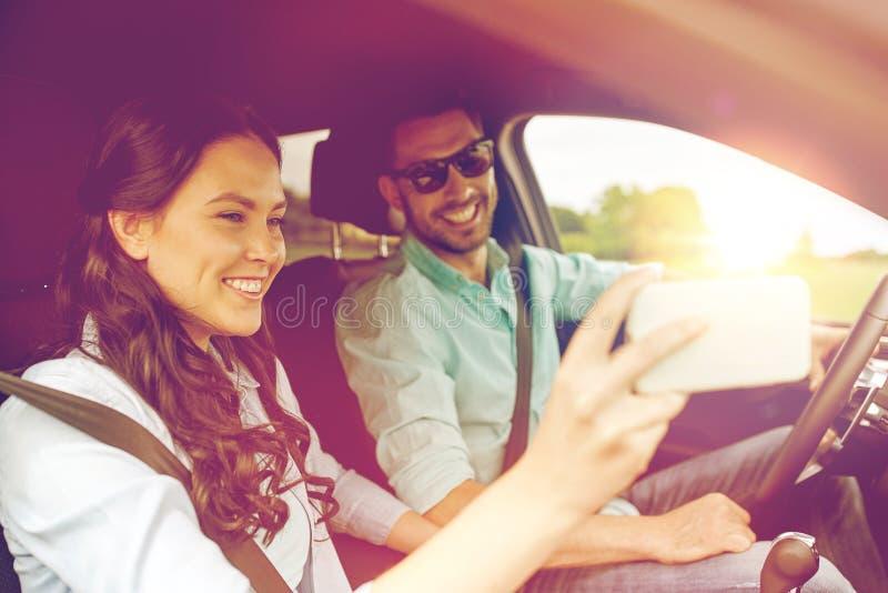 Pares felices en el coche que toma el selfie con smartphone imágenes de archivo libres de regalías