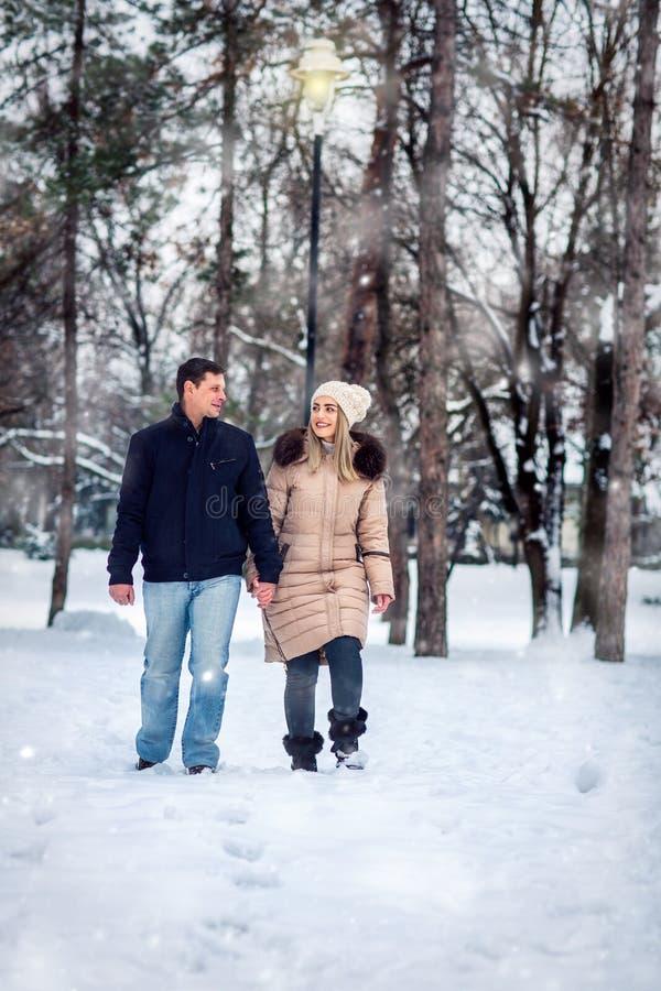 Pares felices en el parque del invierno que se divierte vacaciones de invierno, Christm fotos de archivo libres de regalías