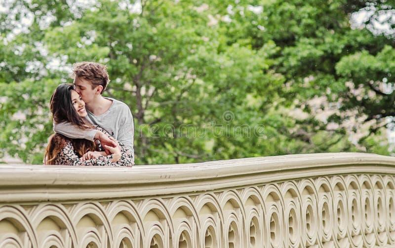 Pares felices en el puente del arco en Central Park fotos de archivo libres de regalías