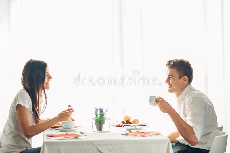 Pares felices en el restaurante que come el almuerzo El hablar sobre comida Tablero completo del hotel, toda la estancia inclusiv imagen de archivo libre de regalías