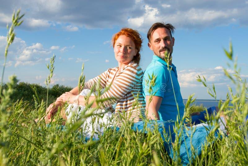 Pares felices en hierba del verano en fondo del cielo Junto hombre y mujer que se sientan en campo foto de archivo libre de regalías
