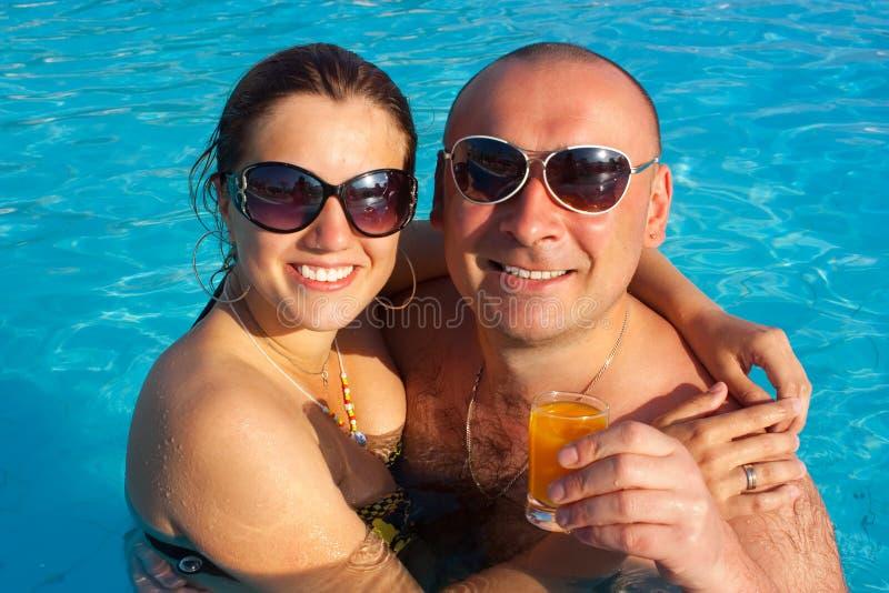 Pares felices en la piscina foto de archivo