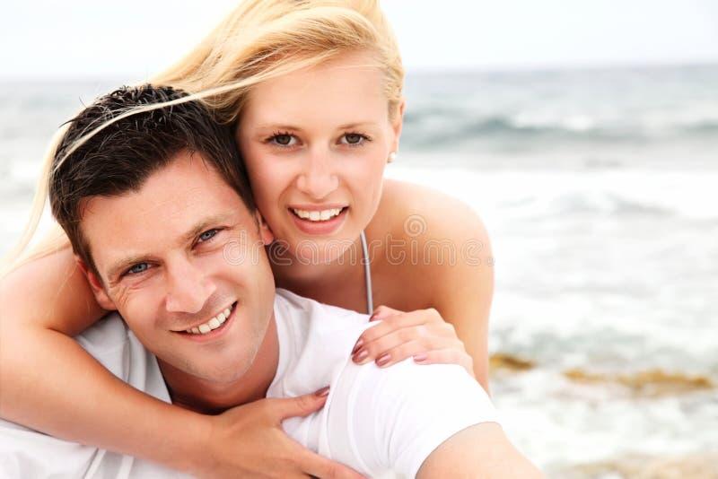 Pares felices en la playa imagen de archivo libre de regalías