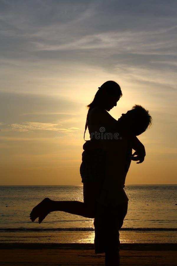 Pares felices en la playa de la puesta del sol - silueta foto de archivo libre de regalías