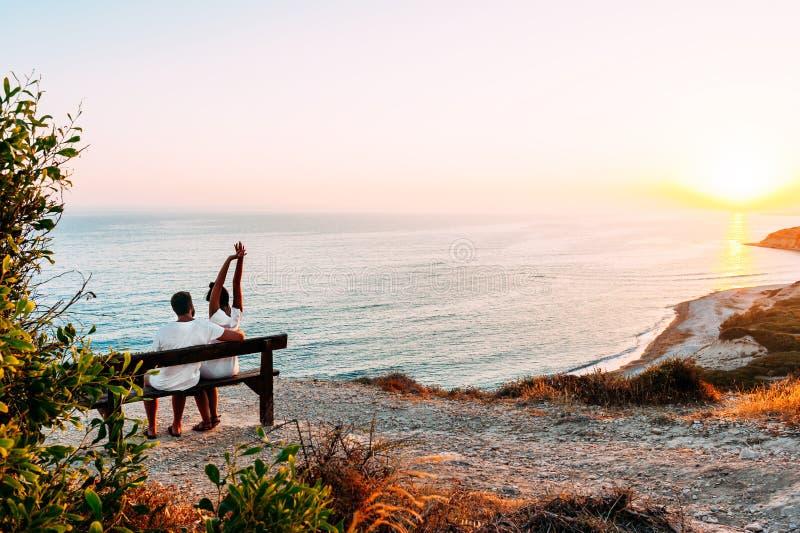 Pares felices en la puesta del sol Hombre y mujer en el amanecer Pares que se sientan en un banco por el mar Júntese en el amor q imagenes de archivo