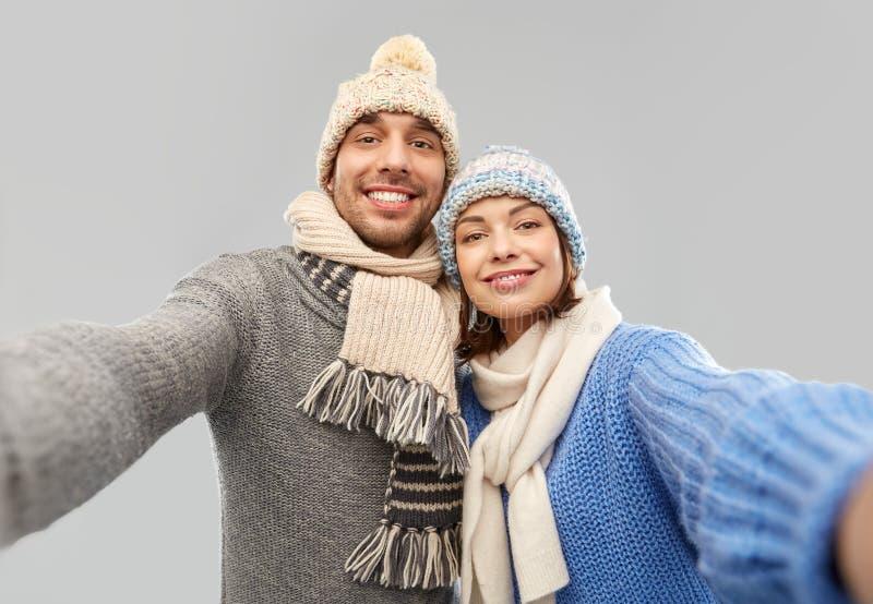 Pares felices en la ropa del invierno que toma el selfie foto de archivo