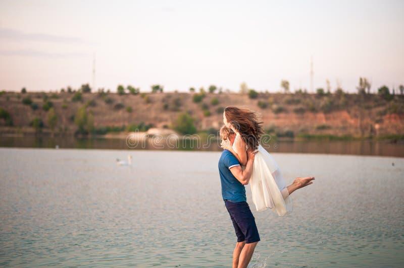Pares felices en los abrazos de la puesta del sol en el agua Un hombre cría a una mujer en sus brazos y la vuelve en un río fotografía de archivo libre de regalías