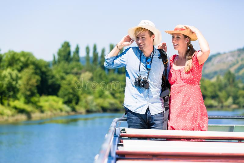 Pares felices en los sombreros del sol de la travesía del río que llevan en verano imagen de archivo