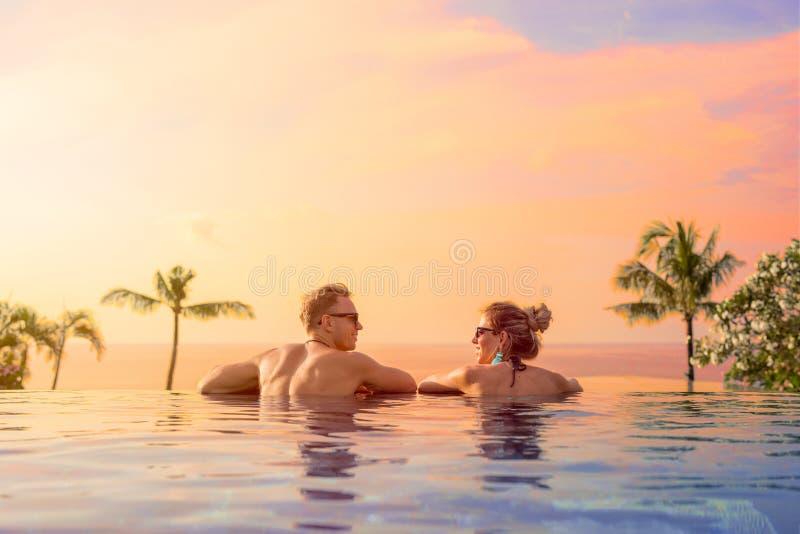 Pares felices en luna de miel en piscina del hotel de lujo imagen de archivo