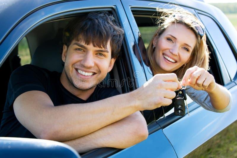 Pares felices en nuevo coche fotografía de archivo
