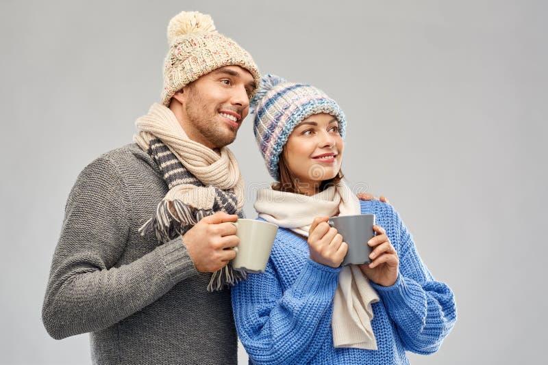 Pares felices en ropa del invierno con las tazas imagenes de archivo