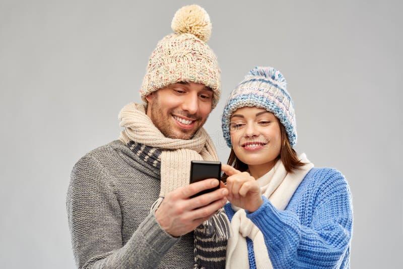 Pares felices en ropa del invierno con smartphone foto de archivo