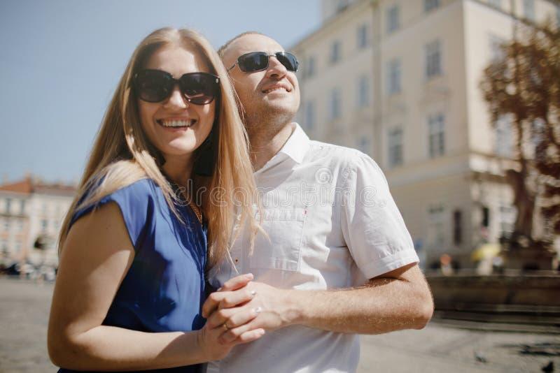Pares felices hermosos que abrazan en la ciudad imagen de archivo libre de regalías