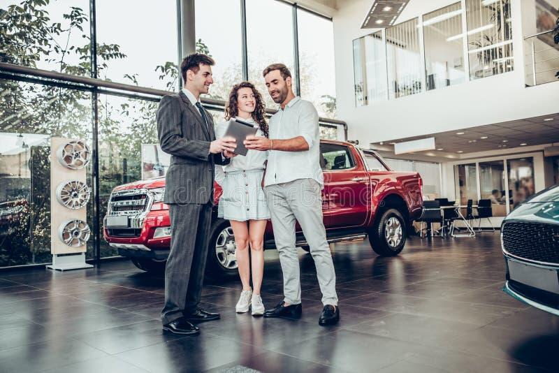Pares felices hermosos que compran un coche en el vendedor de coches hermoso de la sala de exposición del salón del coche que mue imagenes de archivo