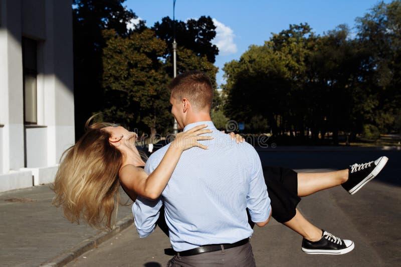 Pares felices, hombre y mujer, sonriendo el hombre lleva a cabo la mujer y vueltas imagen de archivo