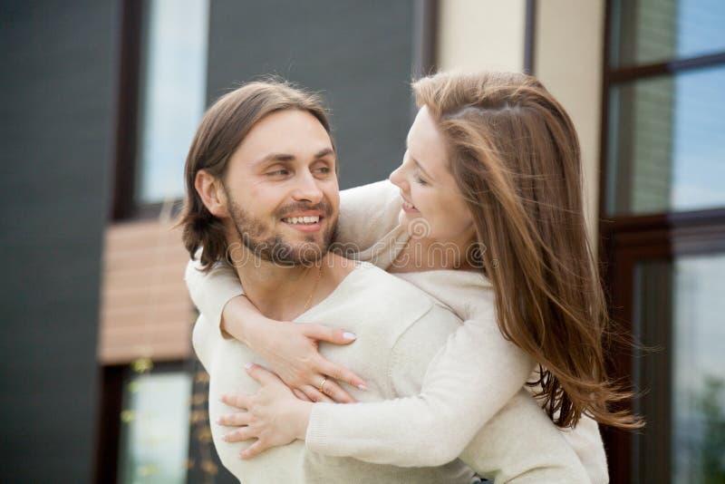 Pares felices jovenes cariñosos que abrazan el cerdo al aire libre, sonriente del marido imágenes de archivo libres de regalías