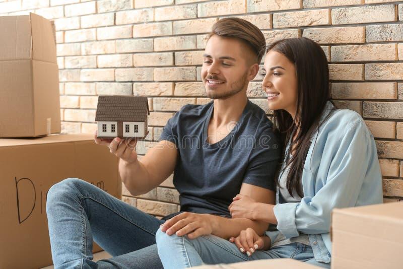 Pares felices jovenes con el modelo de la casa y las cajas móviles que se sientan en piso en el nuevo hogar imagen de archivo libre de regalías