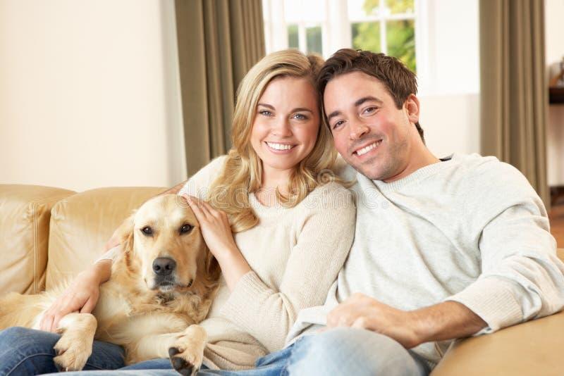 Pares felices jovenes con el perro que se sienta en el sofá fotos de archivo libres de regalías