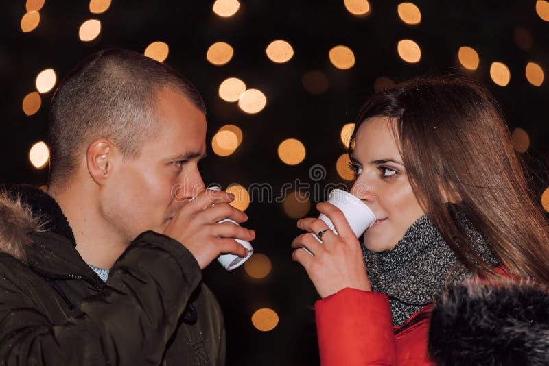 Pares felices jovenes con las bebidas calientes en una víspera del invierno imagen de archivo