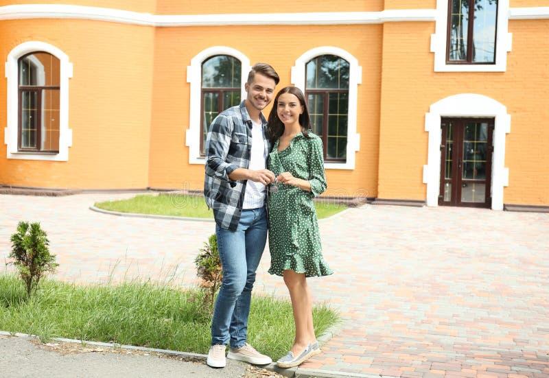 Pares felices jovenes con llave cerca de su nueva casa al aire libre fotos de archivo libres de regalías