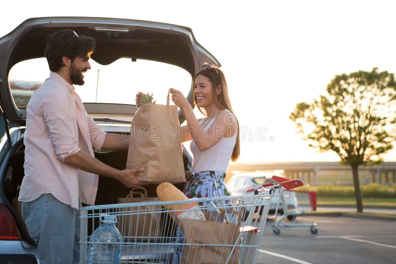 Pares felices jovenes delante de un supermercado en el estacionamiento foto de archivo