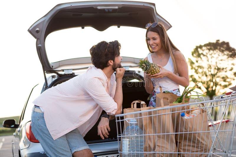 Pares felices jovenes delante de un supermercado en el estacionamiento fotografía de archivo