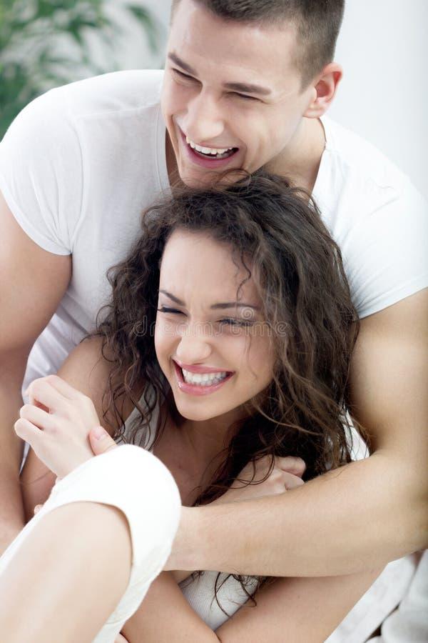 Pares felices jovenes en cosquillas del amor foto de archivo