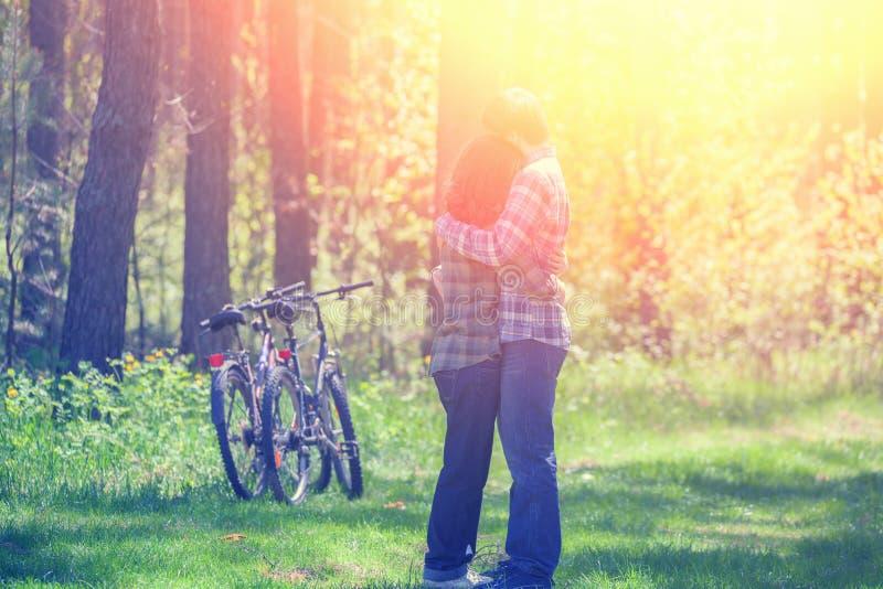 Pares felices jovenes en el amor que abraza en el bosque imagen de archivo