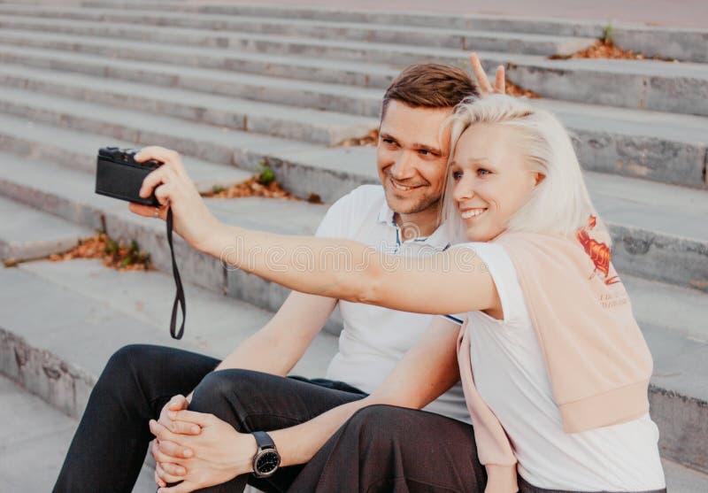 Pares felices jovenes en el amor que hace el selfie en cámara retra en la calle de la ciudad fotografía de archivo