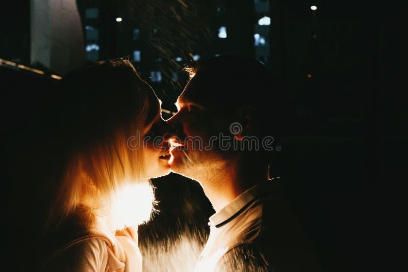 Pares felices jovenes en el amor que se besa en noche debajo de la lluvia Foto con efectos de destello imágenes de archivo libres de regalías