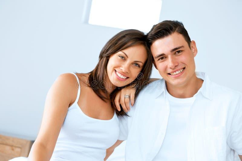 Pares felices jovenes en el dormitorio imagenes de archivo