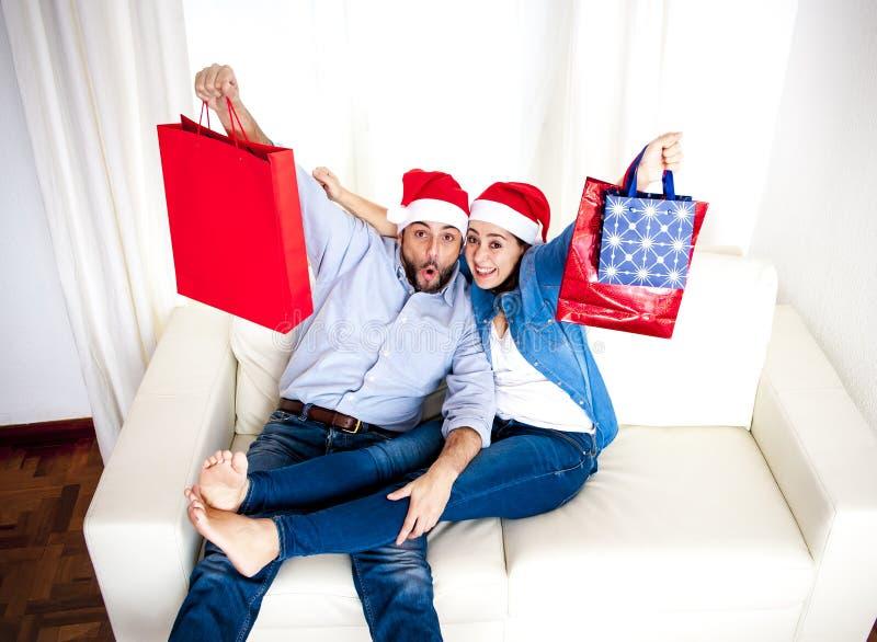 Pares felices jovenes en el sombrero de Papá Noel en la Navidad que sostiene los panieres con los presentes imagenes de archivo