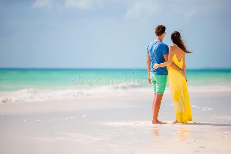 Pares felices jovenes en la playa blanca en las vacaciones de verano fotografía de archivo