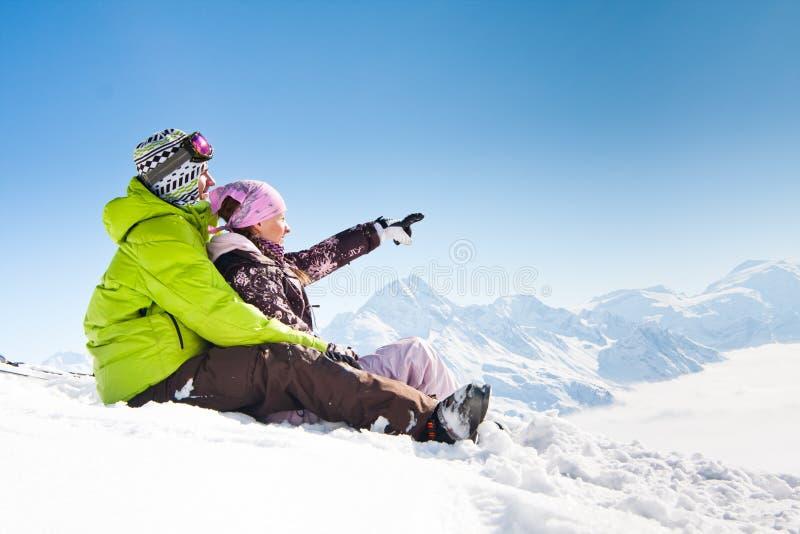 Pares felices jovenes en montañas del invierno imagenes de archivo