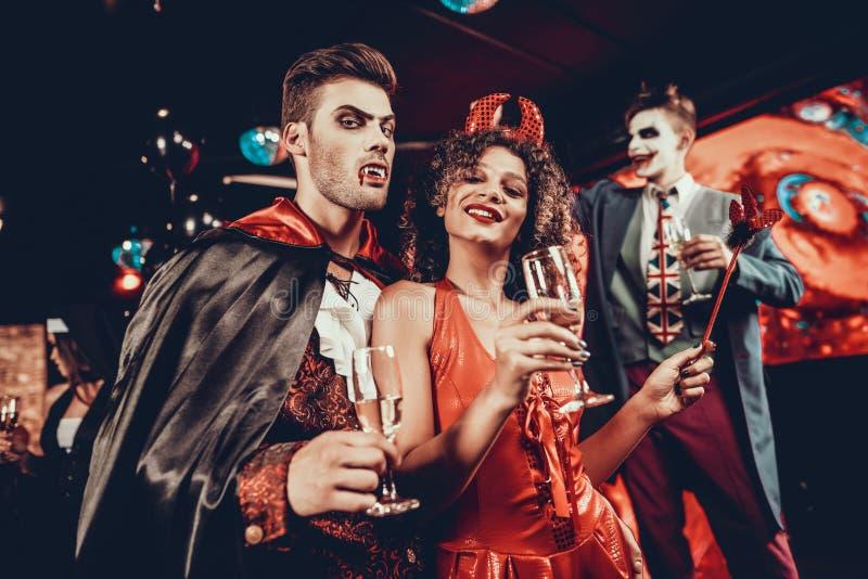 Pares felices jovenes en trajes en el partido de Halloween foto de archivo